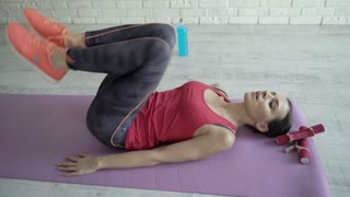 Young, pretty woman doing sit-ups on mat at home, 4K