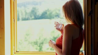 Young, pretty woman drinking water and enjoying beautiful view from the window