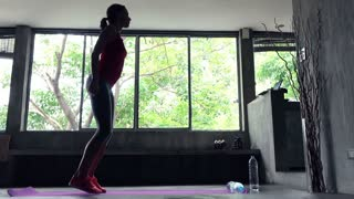 Young, pretty woman exercising, doing jumping at home