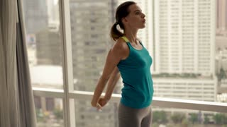 Young, pretty woman exercising, stretching her arms on mat by the window, 4K