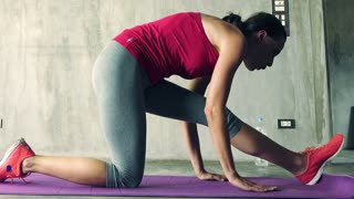 Young, pretty woman exercising, stretching her legs on mat at home
