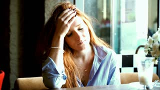 Young, pretty woman having headache in cafe