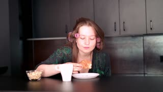 Young pretty woman in bathrobe and hair rollers eating delicious croissant in the kitchen