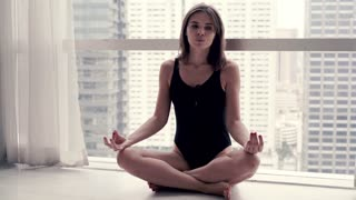 Young, pretty woman meditating at home