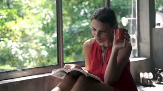 Young, pretty woman reading book and drinking coffee by window, 4K