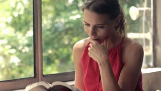 Young, pretty woman reading book and drinking coffee by window