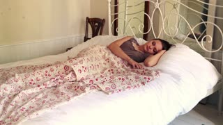 Young, pretty woman sleeping on bed in stylish bedroom