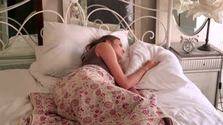Young, pretty woman turn off clock and sleeping on bed in  bedroom