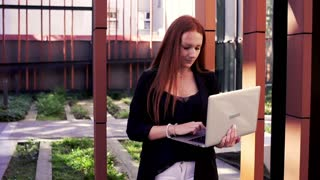 Young, pretty woman with red hair finish working on laptop and go away