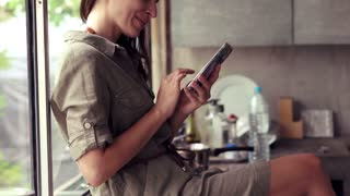 Young, pretty woman with smartphone sitting in the kitchen
