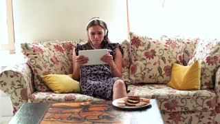 Young, sad girl watching movie on tablet sitting at sofa