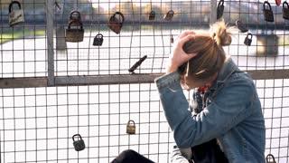 Young sad woman sitting on the bridge with symbol of lock love
