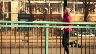 Young, sportive woman jogging in the city, super slow motion