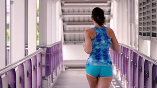 Young, sportive woman jogging on the bridge the city, super slow motion
