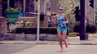 Young, sportive woman jogging on the street in the city, super slow motion