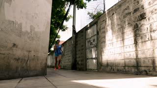 Young, sportive woman jogging sidewalk in the city, super slow motion