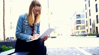 Young student sitting with notes on the bench in the city