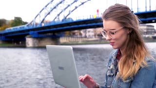 Young teen girl sitting with laptop close to the river.
