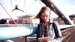 Young teen girl standing with tablet on the bridge in the city