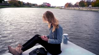 Young teen girl texting on smartphone close to the river