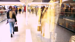 Young teenager girl using mobile phone at shopping mall