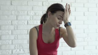 Young tired woman having shoulder pain after exercises at home