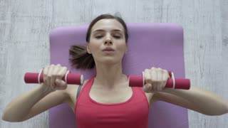 Young woman doing arms exercise with dumbbell at home