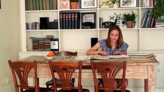 Young woman doing notes while learning by table at home