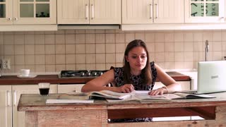 Young woman doing notes while learning by table in the kitchen