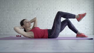 Young woman doing stomach exercise on mat on floor at home, 4K