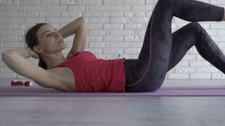 Young woman doing stomach exercise on mat on floor at home