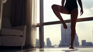Young woman doing yoga pose, by the window with city view