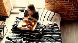 Young woman eating breakfast sitting on bed at home