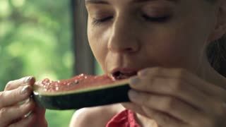 Young woman eating watermelon super slow motion