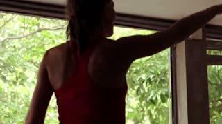 Young woman exercising kicks at home