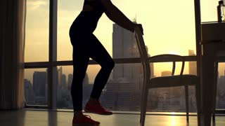 Young woman exercising legs on chair at home during sunset