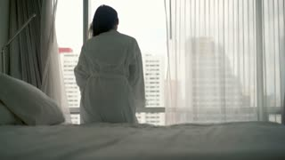 Young woman in bathrobe stretching her arms behind window, 4K