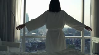 Young woman in bathrobe stretching her arms behind window