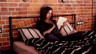 Young woman in pajamas watching film on tablet on bed