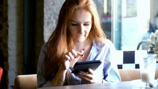 Young woman in red hair sitting in e-book in cafe