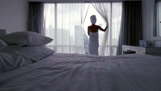 Young woman in towel  unveil curtains and admire city super slow motion