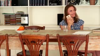 Young woman listen to music sitting by table at home