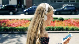 Young woman listen to music while sitting in the city