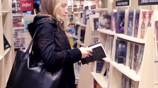 Young woman looking book in bookstore