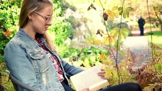 Young woman reading book in beautiful garden
