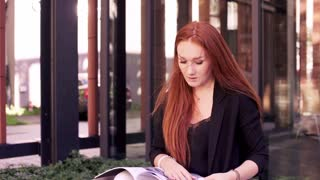 Young woman reading manual on the bench in the city