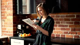 Young woman reading newspaper in the morning