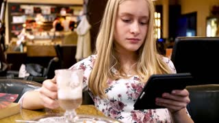 Young woman reading something on e-book sitting in cafe
