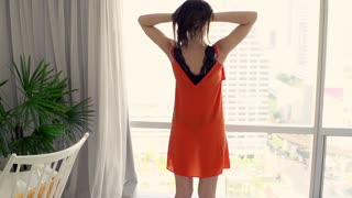 Young woman stretching her arms behind window with splendid city view, super slow motion