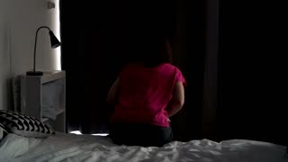 Young woman unveil curtains in bedroom